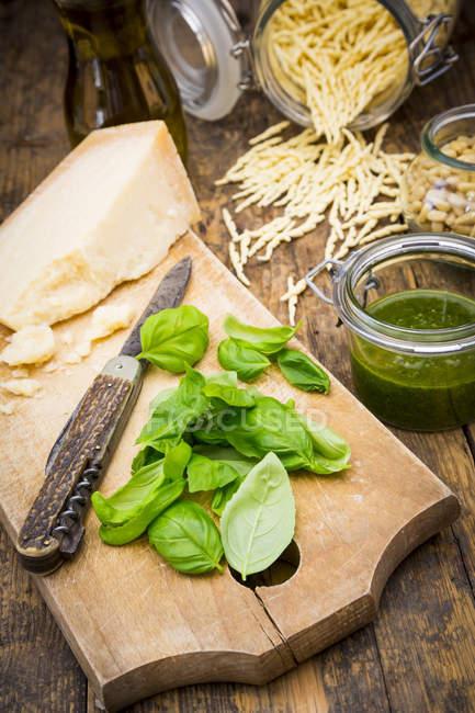 Песто Алла Дженовезе, васильок листя, Пармезан, кедрові горіхи, оливкове масло і сирого trofie локшину на дерев'яні таблиці — стокове фото