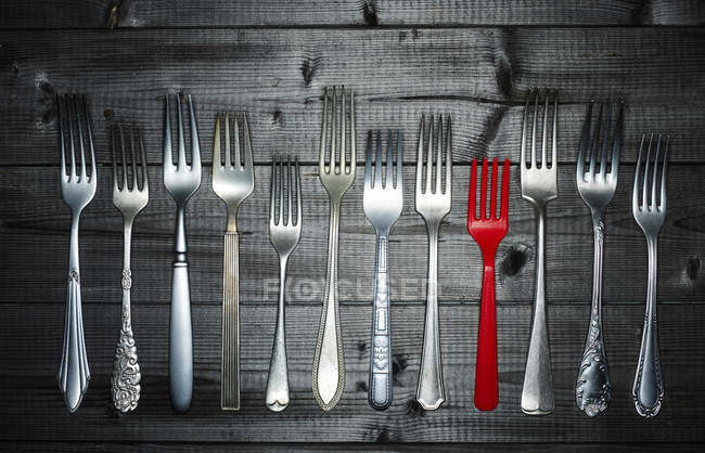 Row of different silver forks and a red plastic fork on wood — Stock Photo