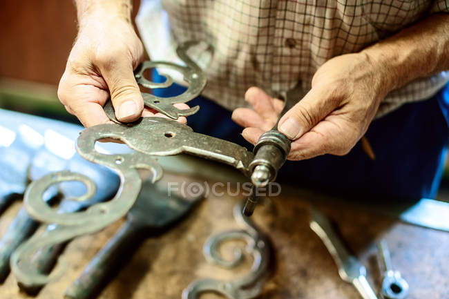 Close-up of male hands holding handcrafted hinges — Stock Photo