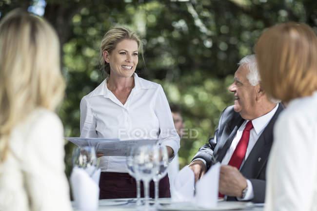 Cameriera, dando i menu ai clienti al tavolo — Foto stock