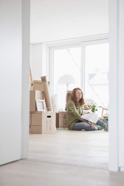 Jeune femme dans le nouvel appartement avec des boîtes en carton, en regardant le plan de sol — Photo de stock
