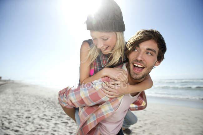 Молодой человек таскает подружку на пляже — стоковое фото
