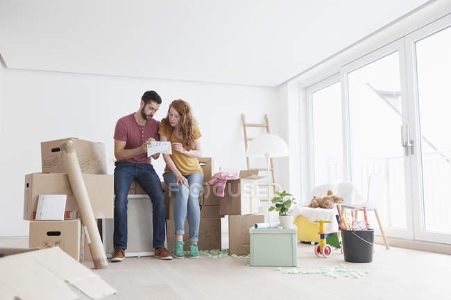 Pareja joven en piso nuevo con cajas de cartón mirando el plano - foto de stock