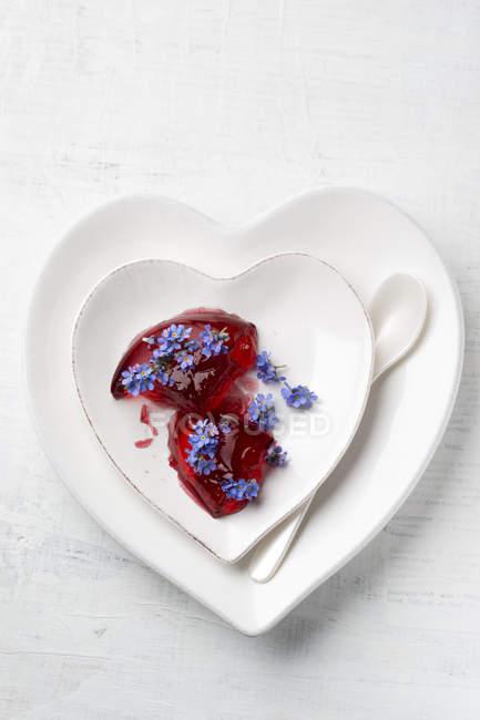 Coração em forma de placas de gelatina vermelha, guarnecido com Miosótis — Fotografia de Stock