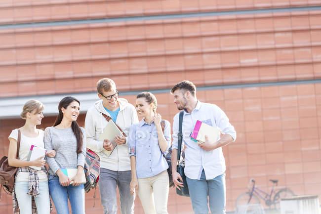 Gruppo di allievi con i libri a camminare e parlare all'aperto — Foto stock