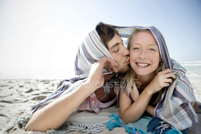Happy young couple lying on beach kissing under a blanket — Stock Photo