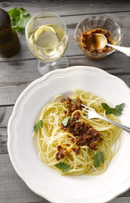 Блюдо из спагетти с томатным соусом песто и стакан белого вина — стоковое фото