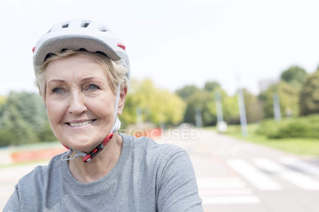 Portrait of smiling senior woman wearing cycling helmet — Stock Photo
