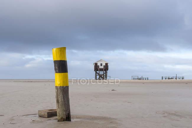 Германии, в земле Шлезвиг-Гольштейн, St Peter-Ording, дом на сваях на пляже в дневное время — стоковое фото