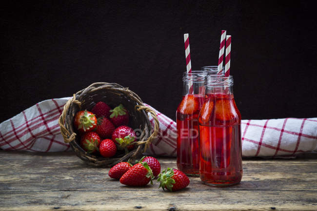 Three glass bottles of homemade strawberry lemonade and wickerbasket of strawberries — Stock Photo