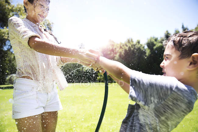 Brother and sister splashing water — Stock Photo