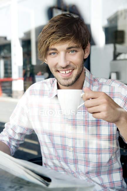 Homem segurando xícara de coofee no café — Fotografia de Stock