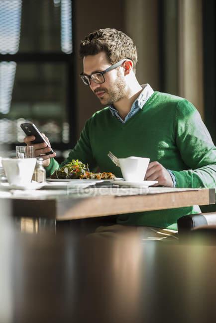Человек сидел в кафе и с помощью мобильного телефона — стоковое фото