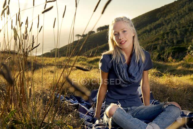 Jeune femme se détendre sur la couverture dans la prairie — Photo de stock