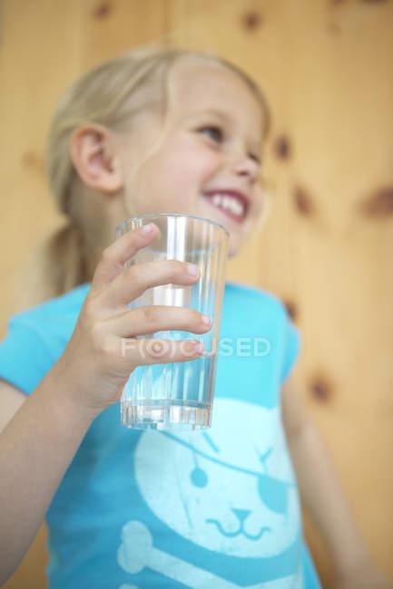 Menina loira feliz segurando vidro de água — Fotografia de Stock