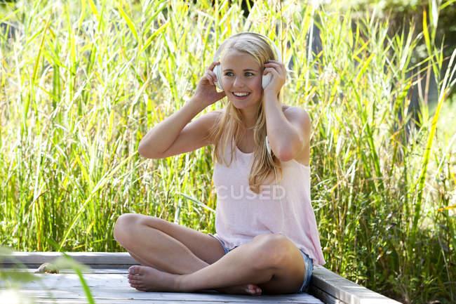 Портрет улыбающейся девушки в наушниках, сидящей на деревянной набережной — стоковое фото