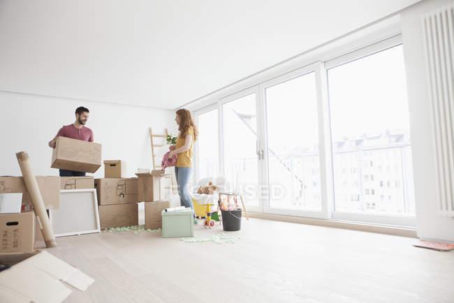 Jeune couple dans de nouvelles boîtes plates en carton de déballage — Photo de stock