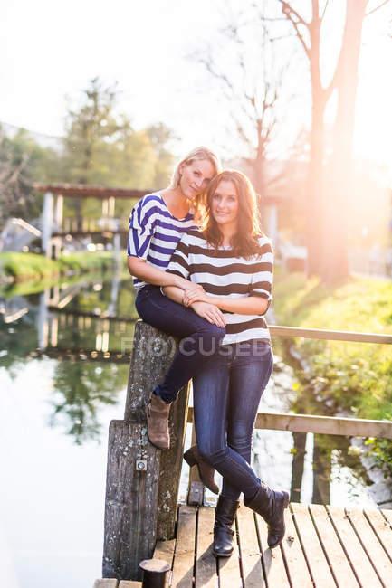 Лесбийская пара смотрит в камеру на пристани — стоковое фото