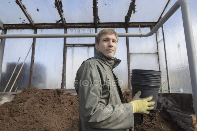 Young gardener at work, holding pots for soil — Stock Photo