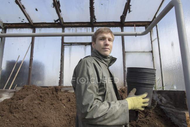Молодий садівник на роботі, проведення горщики для грунту — стокове фото