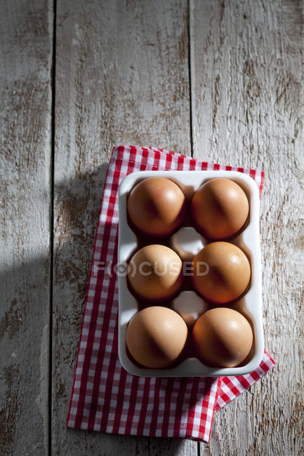 Egg box with six brown hen eggs kitchen towel and wood — Stock Photo