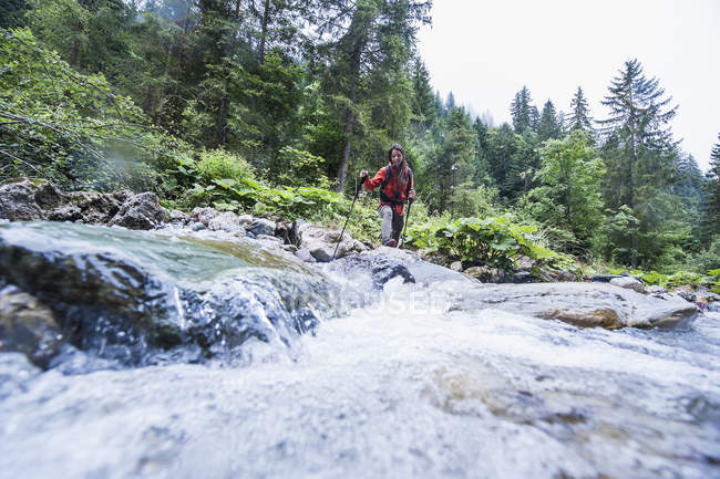 Austria, Altenmarkt-Zauchensee, young female hiker crossing a river — Stock Photo