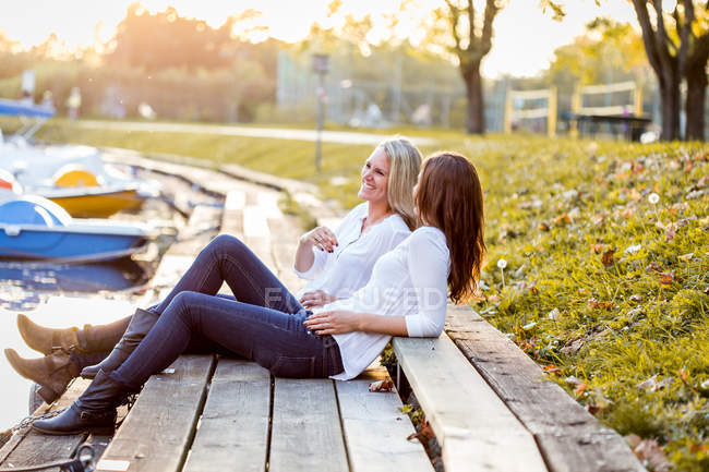 Подруги сидят на набережной — стоковое фото