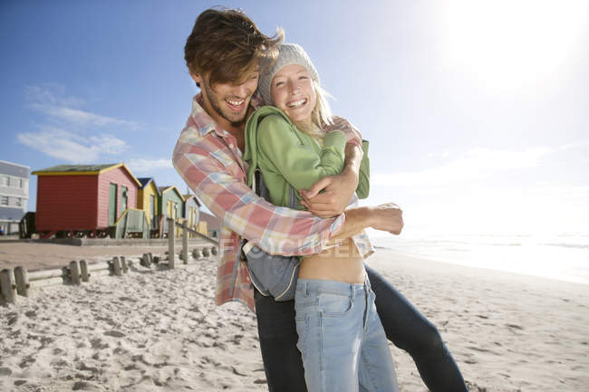 Playful young couple on beach — Stock Photo