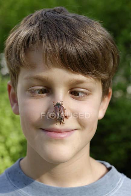 Boy with maybug on his nose — Stock Photo