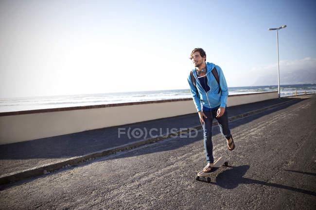 Homem com longboard na estrada costeira — Fotografia de Stock