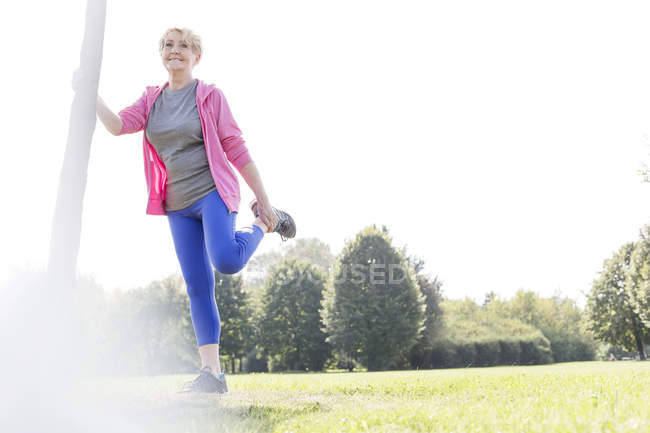 Senior woman leaning on tree trunk doing stretching exercises in a park — Stock Photo