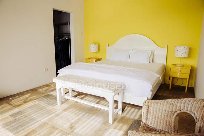 Indonésia, Bali, quarto com parede amarela e amarela cabeceira de uma vivenda de férias — Fotografia de Stock