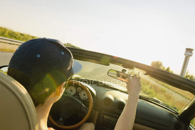 Teenager driving in a convertible car adjusting rear view mirror — Stock Photo