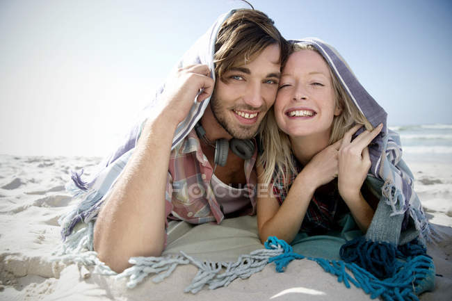 Happy young couple lying on beach under a blanket — Stock Photo
