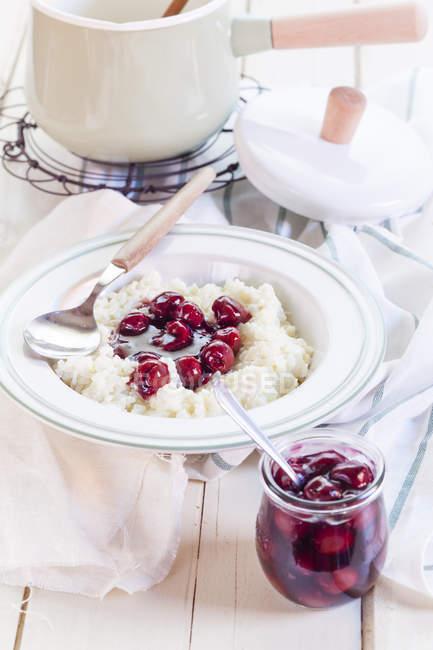 Рисовый пудинг с вишневым соусом на плите — стоковое фото