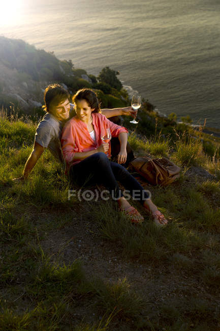 Couple with white wine relaxing at coast — Stock Photo