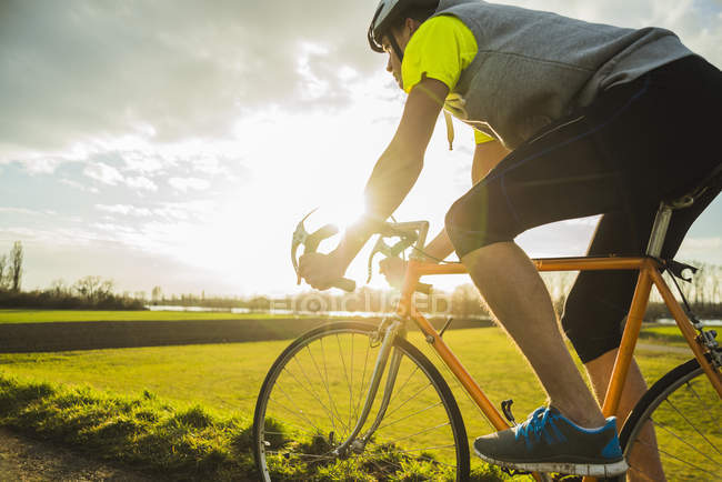 Young man riding bicycle at the sunset — Stock Photo