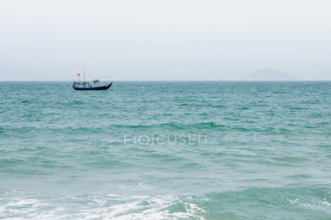 В'єтнамська ловлячий рибу човен, Тихий океан і корабель над поверхнею води — стокове фото