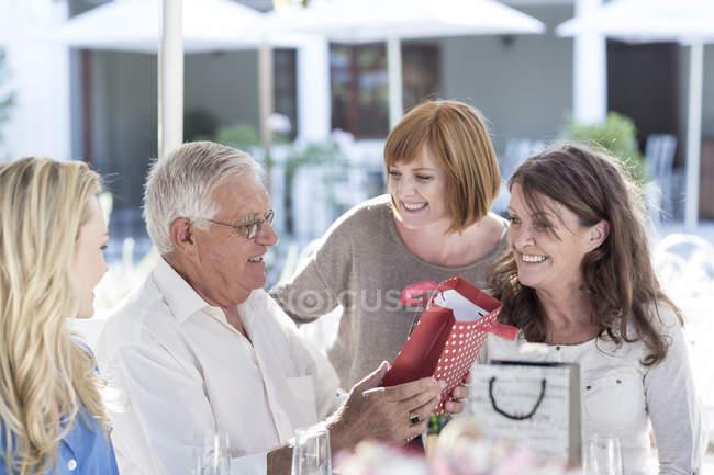 Family celebrating grandfathers birthday at restaurant — Stock Photo
