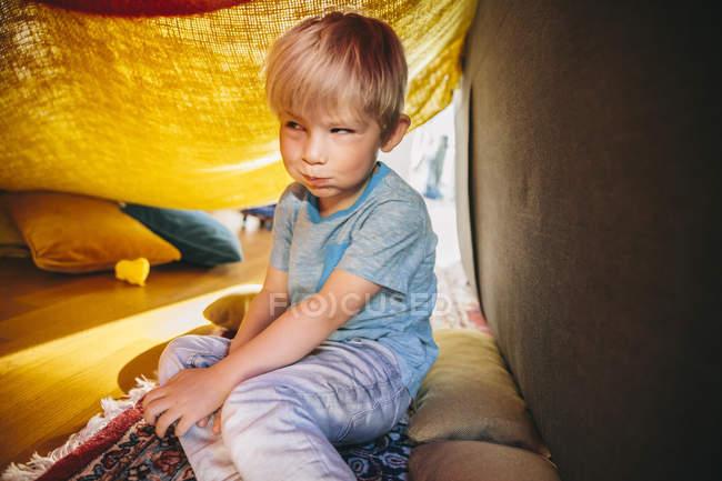 Retrato de menino sentado em uma caverna de cobertor, fazendo uma cara engraçada — Fotografia de Stock