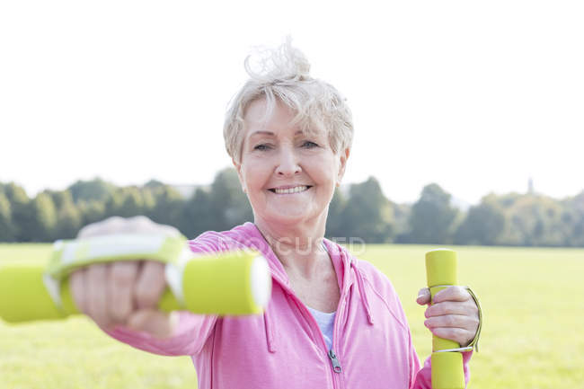 Portrait of senior woman training with dumbbells in a park — Stock Photo