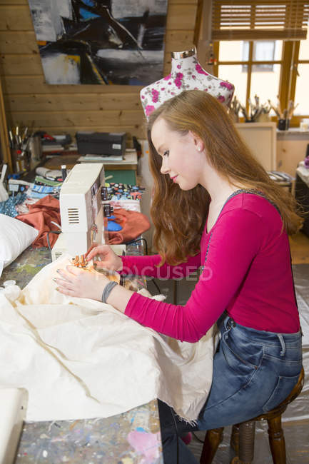 Женщина-подросток, использующая швейную машинку в мастерской — стоковое фото