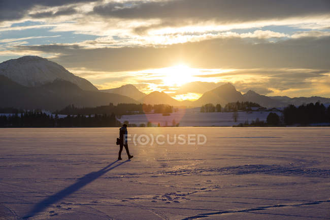Germany, Hopfensee, woman strolling in winter landscape at sunset — Stock Photo