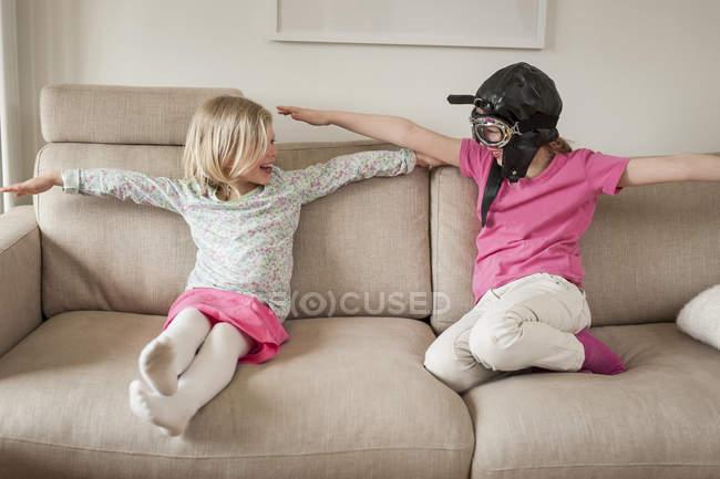 Dos hermanas en el sofá fingiendo volar - foto de stock
