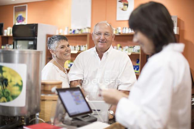 Casal sênior pagando na loja de saúde — Fotografia de Stock