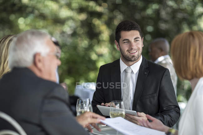 Gens élégants au restaurant extérieur ayant une conversation — Photo de stock
