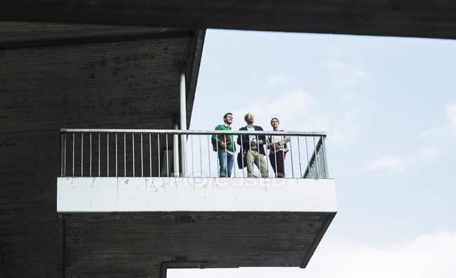 Трое бизнесменов стоят на платформе под мостом — стоковое фото