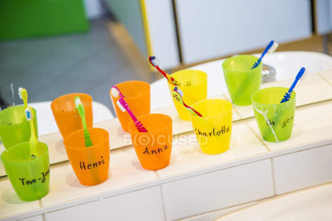Plastic cups with toothbrushes with manes of kids in nursery — Stock Photo