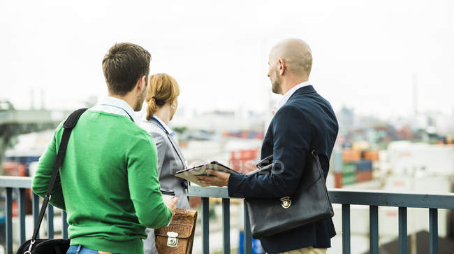 Three businesspeople outdoors looking around — Stock Photo
