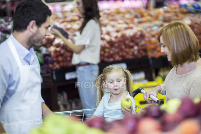 Shop assistant helping customers choosing fruits — Stock Photo